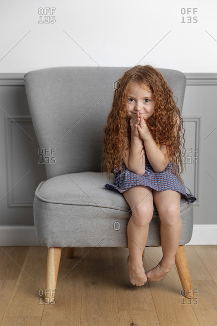 Portrait of cute girl with long hair sitting on chair against wall at home