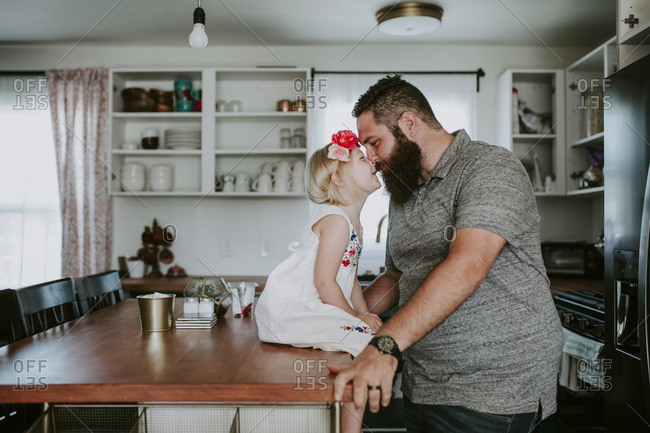 Side view of father and daughter rubbing noses at dining table in kitchen