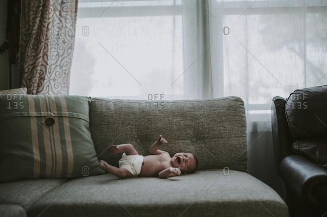 Shirtless newborn baby girl crying while lying on sofa at home