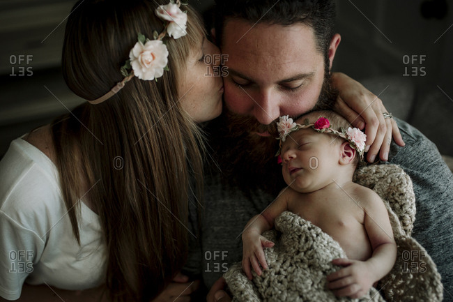 High angle view of wife kissing husband carrying cute sleeping daughter while sitting at home