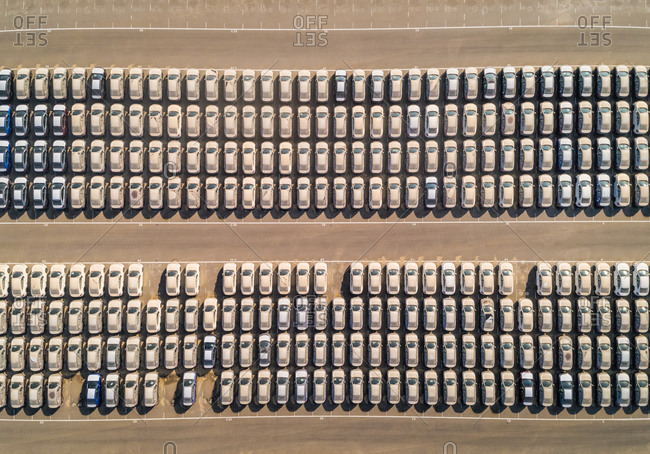 Faraway aerial view of group of cars at parking space on a desert landscape.