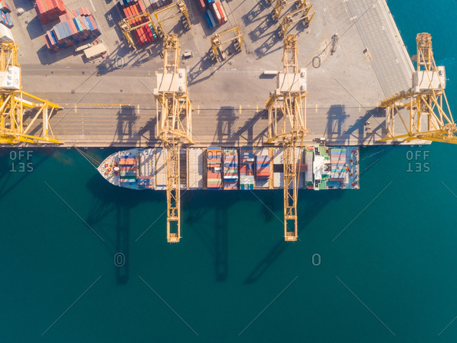 October 5, 2018: Aerial view of a boat being loaded with containers, Dubai, U.A.E.