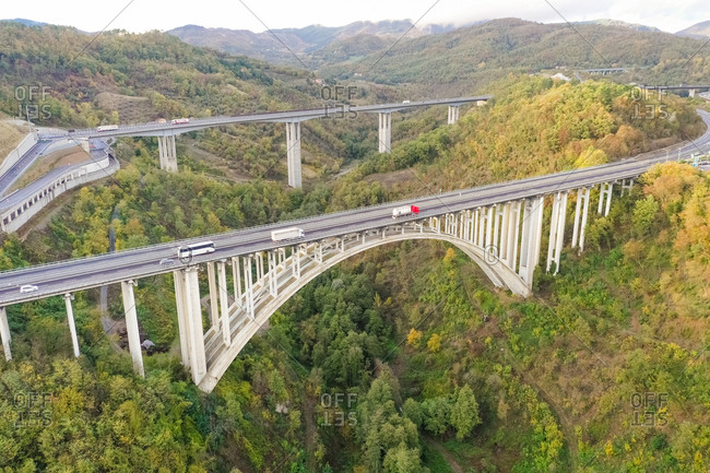 October 30, 2018: Aerial view of arch bridge crossing mountain region, Italy.