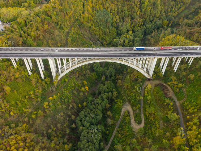 Aerial view of arch bridge crossing mountain region, Italy.