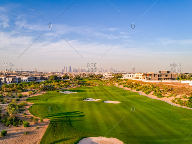 Aerial view of luxury golf club with Dubai at the background, U.A.E.