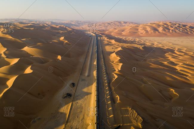 Aerial view of a long train crossing vast desert, U.A.E