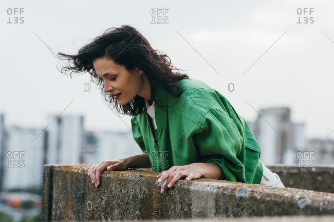 Beautiful smiling woman looking down from the rooftop.