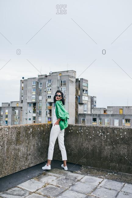 Beautiful woman fashion model posing on building rooftop.