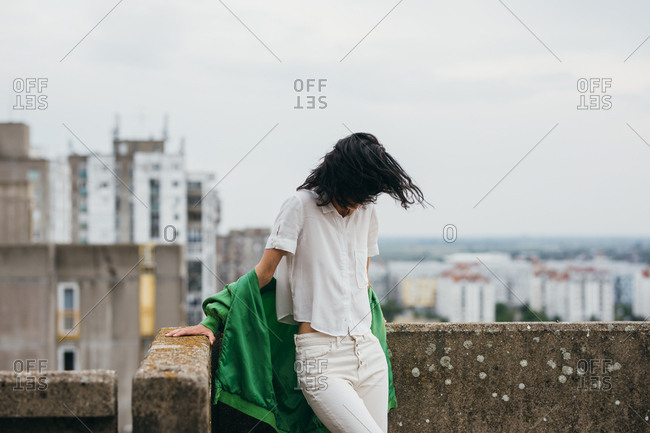 Young stylish urban woman standing on a building rooftop.