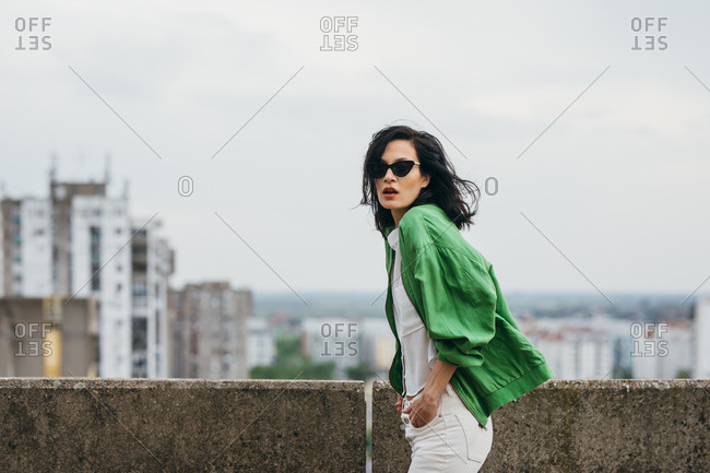 Beautiful attractive woman fashion model  posing on a rooftop wearing green jacket and sunglasses.