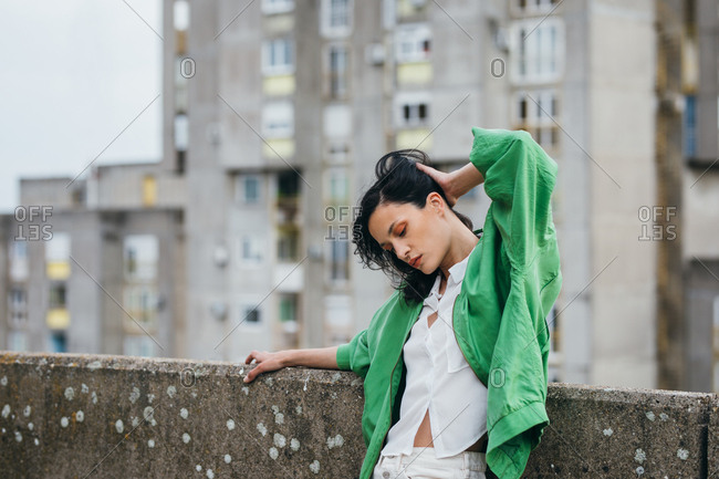Beautiful attractive woman fashion model  posing on a rooftop wearing green jacket.