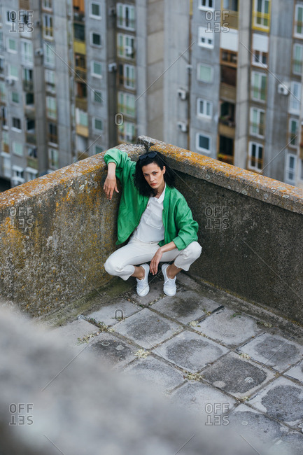Pretty woman fashion model posing on residential building rooftop and looking at camera.