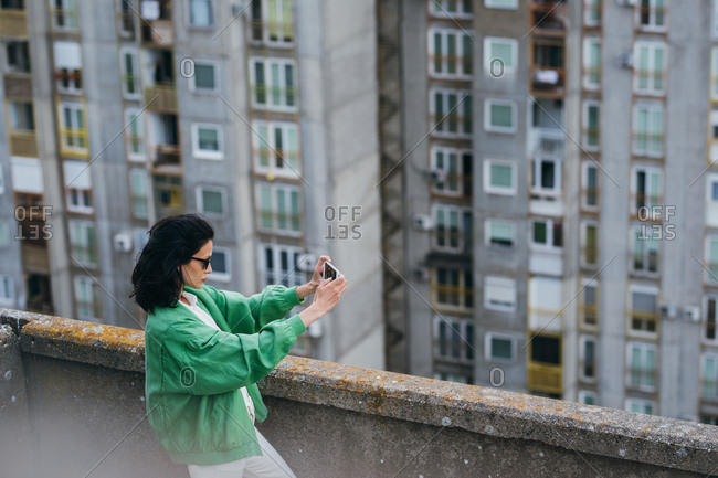 Beautiful Caucasian woman standing on rooftop and taking a photo with her cell phone.