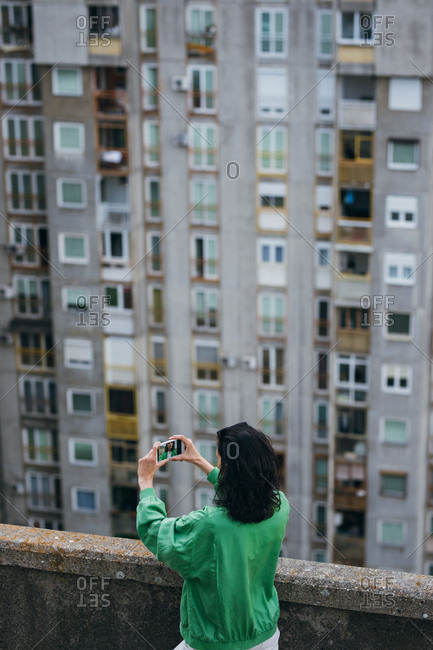 Back view of urban woman standing on residential building rooftop and taking a photo with her cell phone.