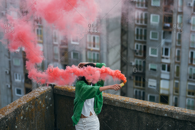 Young woman wearing green jacket holding pink smoke boom on rooftop.