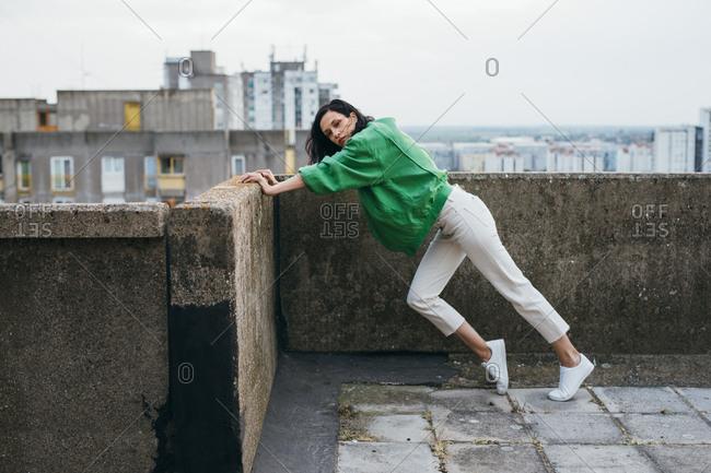 Beautiful woman fashion model posing pushing against a wall.