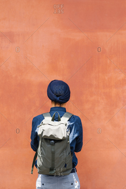 Back view of a man with turban holding backpack.
