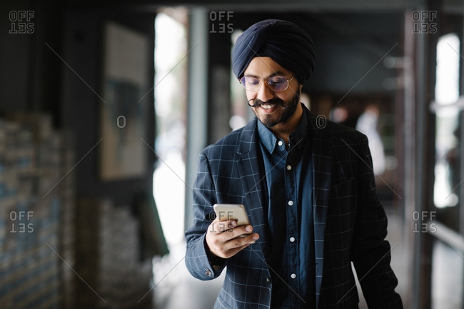 Handsome Indian sikh businessman wearing turban walking and typing on his cell phone.