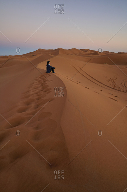 Morocco- woman sitting on desert dune at twilight