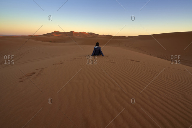 Morocco- back view of woman sitting on desert dune at twilight