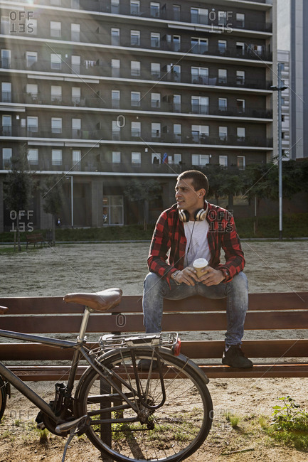 Young man sitting on a bench in the city next to bicycle