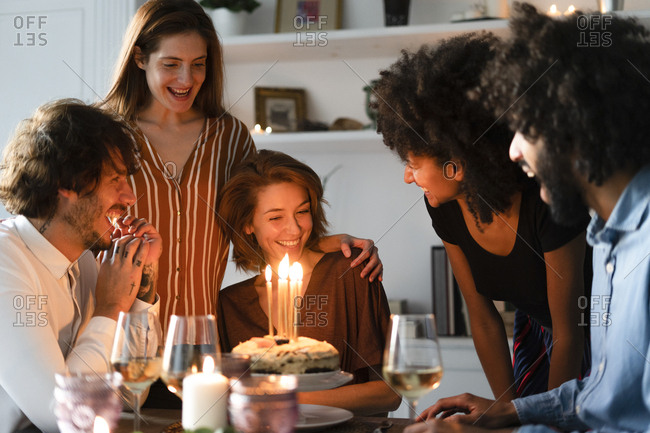 Friends surprising young woman with a birthday cake with burning candles