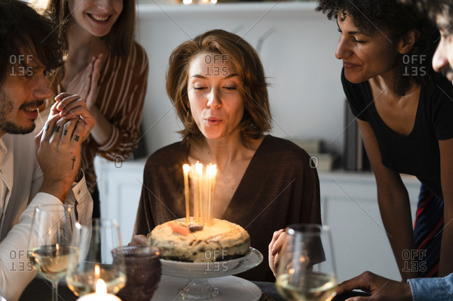 Friends celebrating birthday of a young woman- blowing out birthday candles