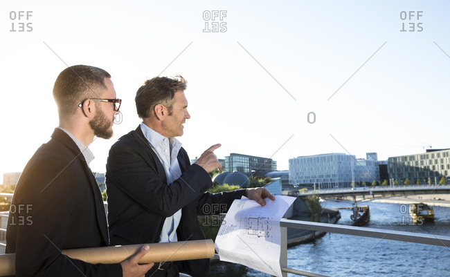Two architects with blueprint discussing on a bridge in the city