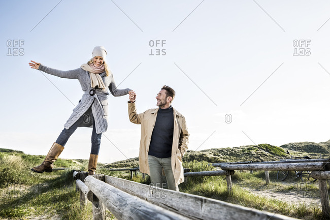 Man helping woman balancing on wooden stakes in dunes