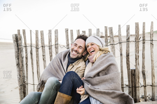 Happy couple wrapped in blanket on the beach