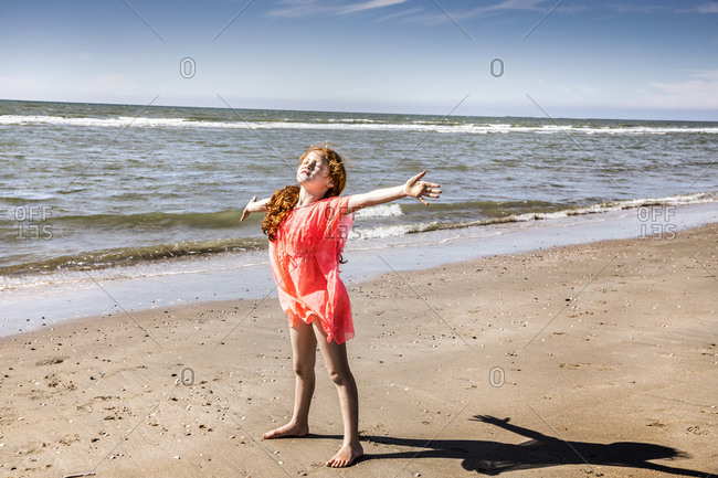 Netherlands- Zandvoort- girl standing on the beach with outstretched arms