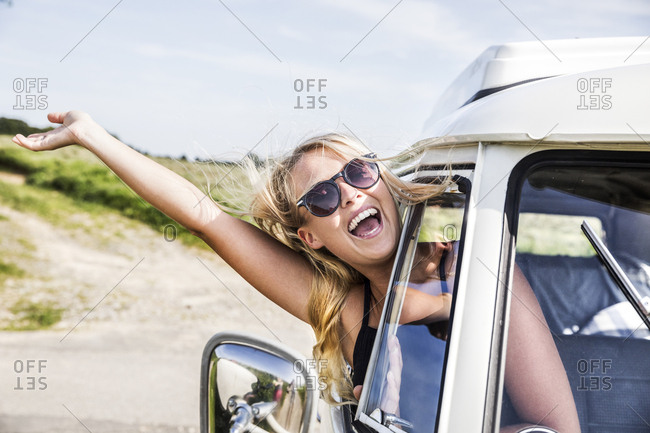 Carefree woman leaning out of window of a van