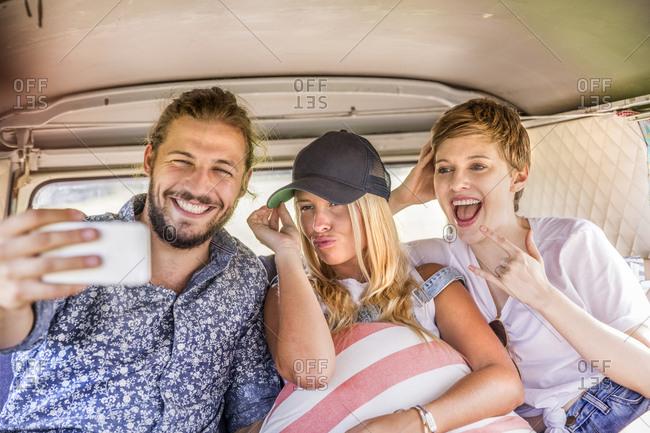 Happy friends inside van taking a selfie