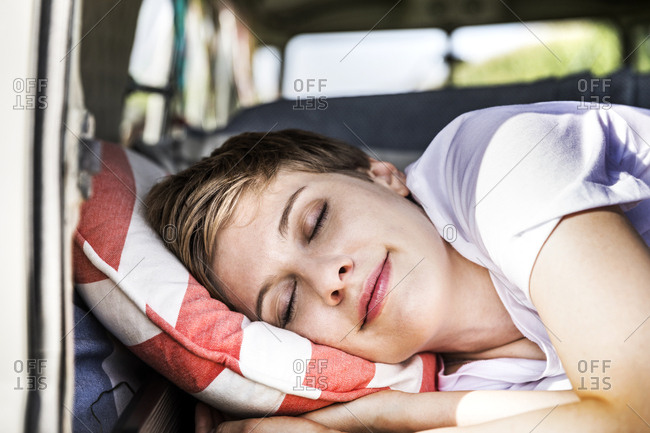 Smiling woman sleeping in a van