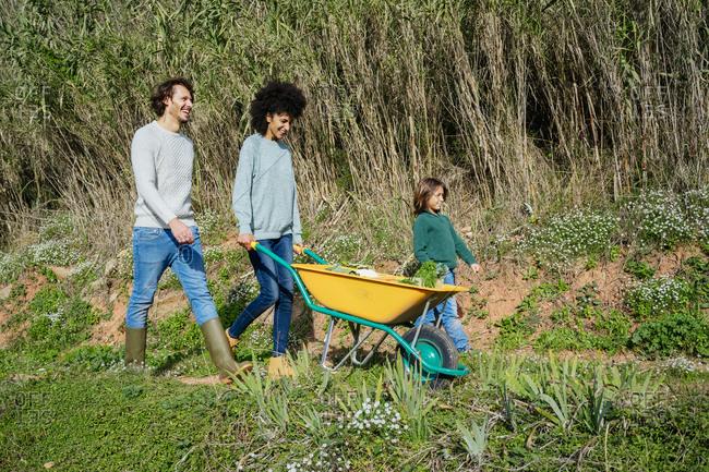 Family walking on a dirt track- pushing wheelbarrow