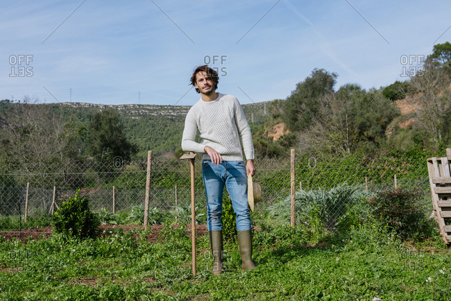 Young farmer standing in vegetable garden with straw hat and a hoe