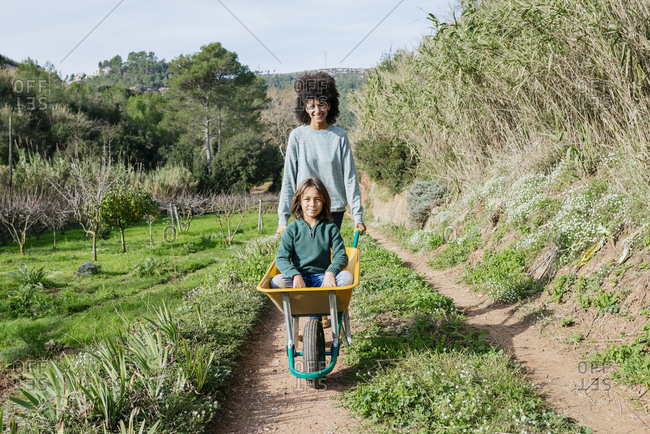 Mother walking on a dirt track- pushing wheelbarrow- with his son sitting in it