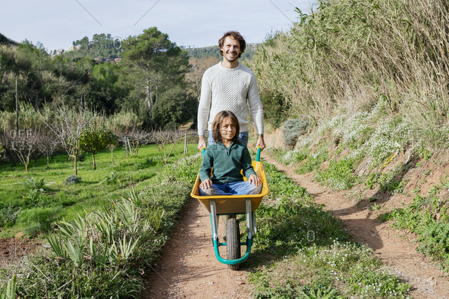 Father walking on a dirt track- pushing wheelbarrow- with his son sitting in it