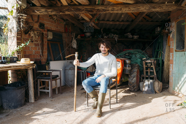 Man with a hoe sitting in a shed with a tractor