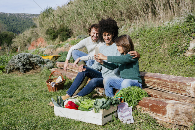 Happy family taking a break after harvesting vegetables- taking selfies