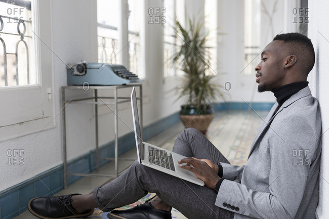 Young businessman sitting on floor in the office working on laptop
