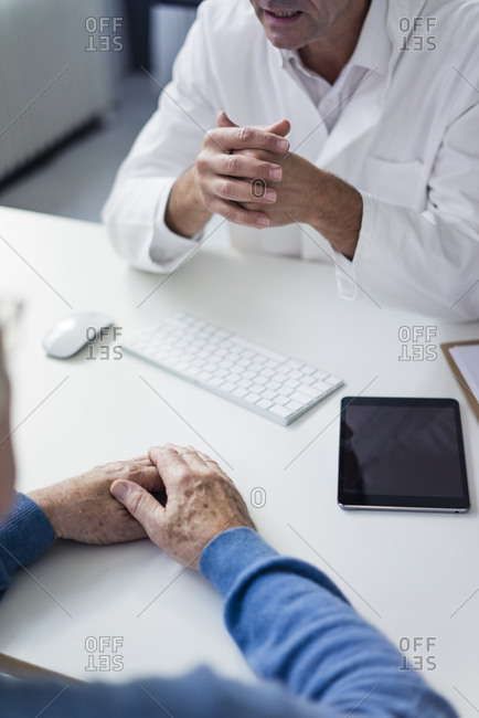 Close-up of doctor talking to senior patient in medical practice