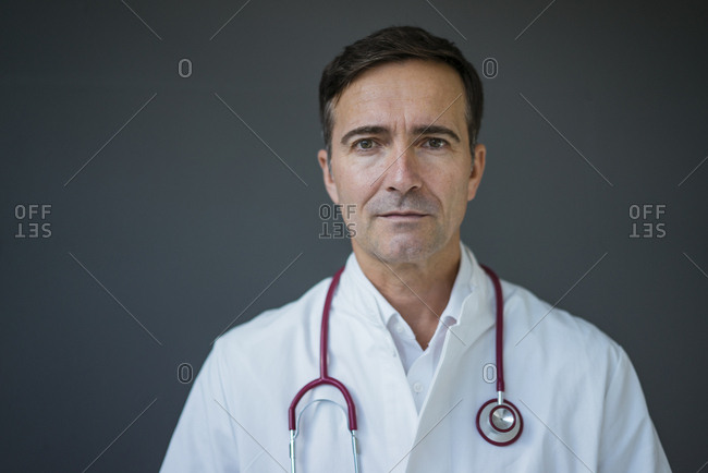 Portrait of doctor at a grey wall