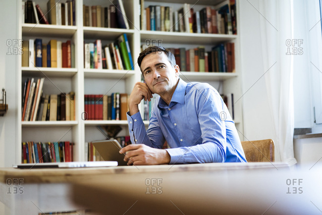 Businessman with tablet sitting at table with bookshelf in background