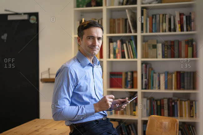 Portrait of confident businessman with tablet leaning at table with bookshelf in background