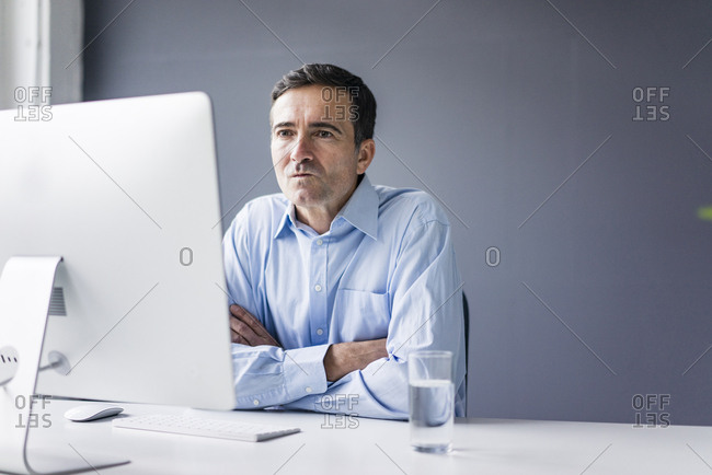 Serious businessman sitting at desk in office looking at computer screen