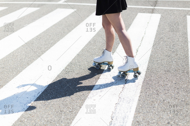 Young woman with roller skates on zebra crossing- partial view