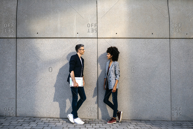 Two colleagues talking outdoors leaning against a wall