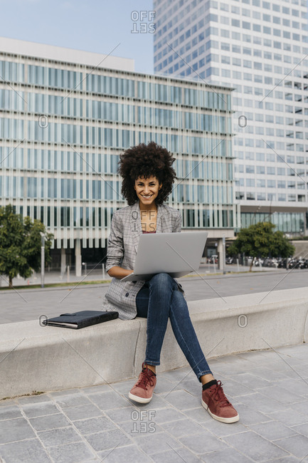 Portrait of smiling businesswoman working with laptop outside office building