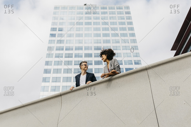 Two colleagues talking outside office building